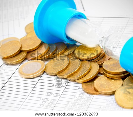 Sand-glass and coins on documents. - stock photo