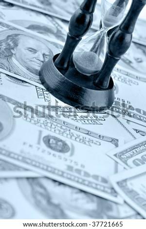 Sand-glass on dollars blue tone - stock photo