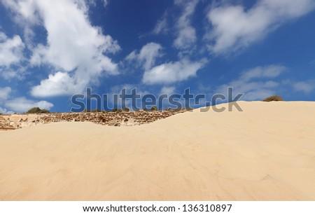 Sand hill,  stone wall,  cloudy sky upward view - stock photo