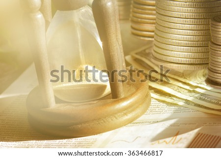 Sand passing through the glass bulbs of an hourglass measuring the passing time. Us dollars and coins on background.  - stock photo