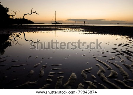 Sand patterns in tidal flat and sailboat at sunset, Florida - stock photo