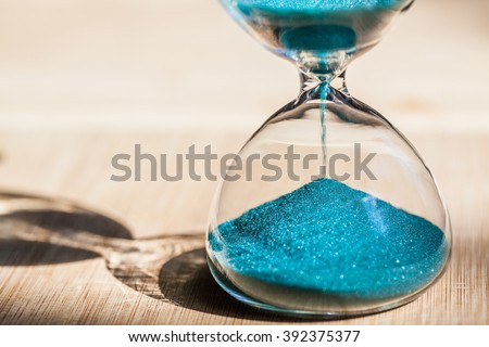 Sand running through the bulbs of an hourglass measuring the passing time in a countdown to a deadline, on a bright wooden background with copy space. - stock photo