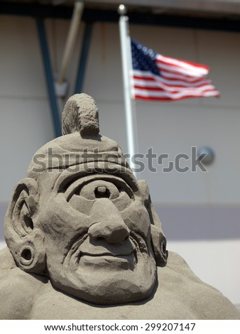 Sand Sculpture of a Cyclops with an American Flag in Background - stock photo