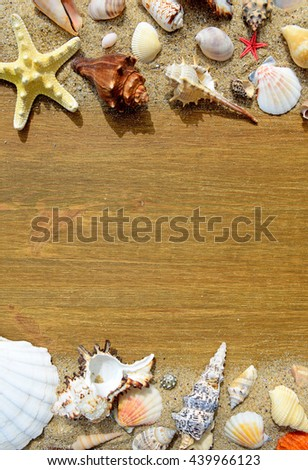 Sand, seashells and starfish on a old wooden background - stock photo