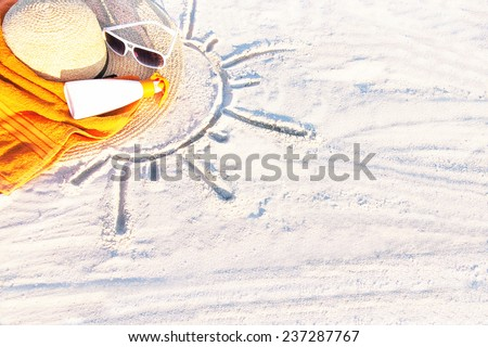 Sand texture (background) with hat, towel, sunscreen (suntan lotion, suncream), sunglasses on the a beach. The sun drawing in the sand. The empty pattern for message. Summer vacations. Copy space.  - stock photo