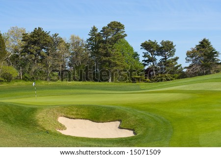 Sand trap and putting green with flag at golf course, country club - stock photo