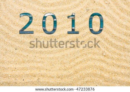 Sand with many lines drawn in it with 2010 written with water, beach background - stock photo