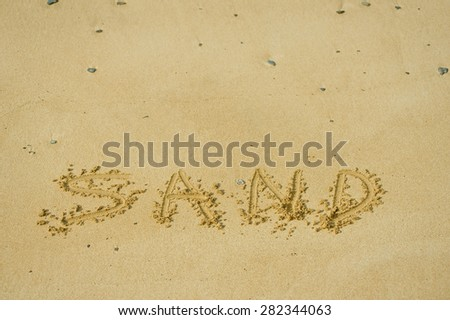 sand written in sand on a beach - stock photo