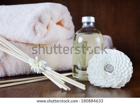 Sandal oil in a bottle and sticks for aromatherapy on wooden surface - stock photo