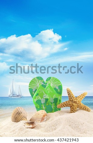 Sandals and seashells in the sand at the ocean - stock photo