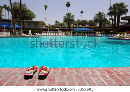 Sandals Next To Large Empty Swimming Pool In Palm Springs, California - stock photo