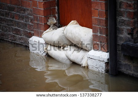 Sandbag barrier in doorway of flooded street in York. - stock photo