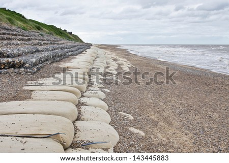 Sandbags and rocks set up as defense against cliff erosion in Suffolk, UK - stock photo