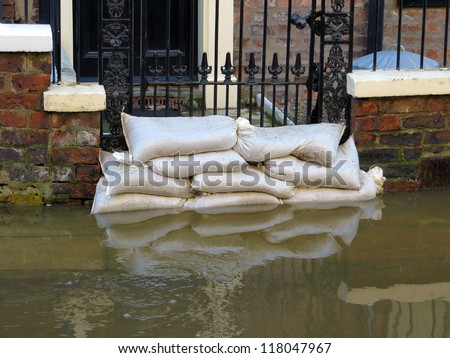 Sandbags stacked in front of house in York flooded street. - stock photo