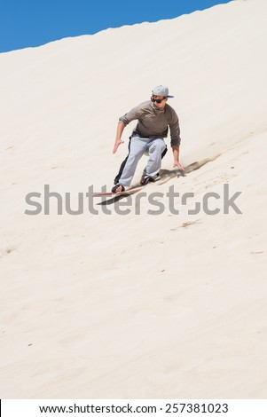 Sandboarding at sand dunes in Little Sahara, Kangaroo Island, South Australia.Focus on the man  - stock photo