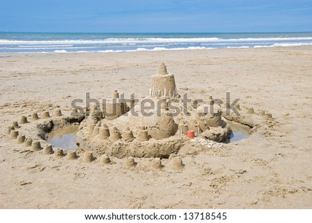 Sandcastle on the beach. Sea on the background - stock photo