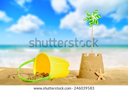 Sandcastle on the beach with pinwheel - stock photo