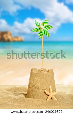 Sandcastle with pinwheel against a beach background - stock photo