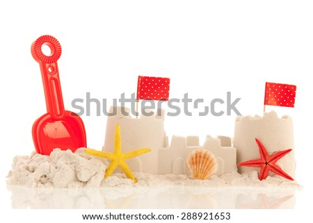 Sandcastle with red toys and flags isolated over white background - stock photo