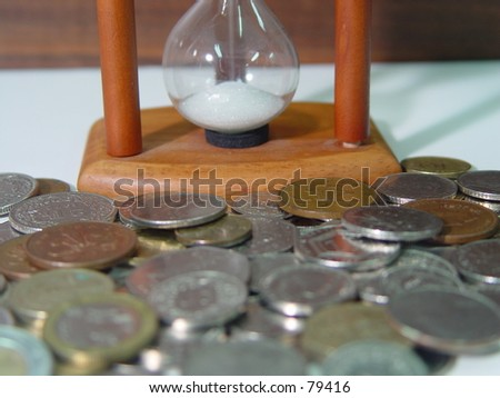 Sandglass and coins - stock photo