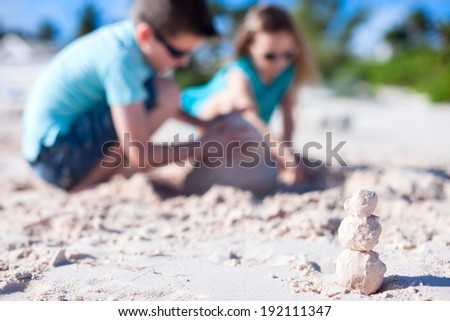 Sandman build from exotic pink sand with two kids building sandcastle on background while on beach holidays - stock photo