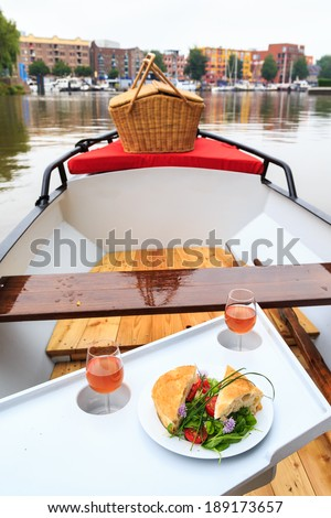 Sandwich and wine on a picnic boat - stock photo