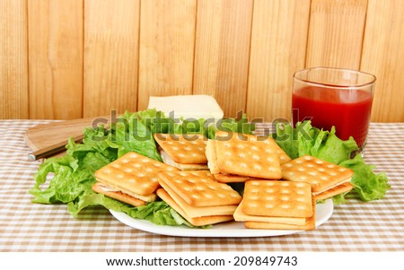 Sandwich crackers with cheese and tomato juice on tablecloth on wooden background - stock photo