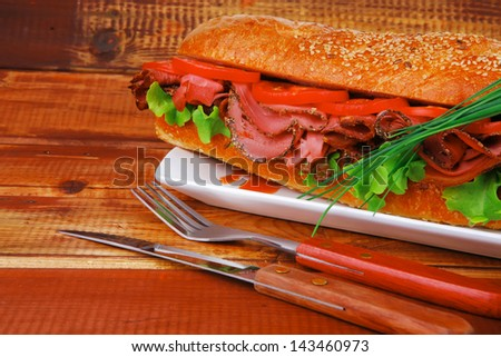 sandwich : fresh french white baguette with chicken smoked sausage on ceramic plate over wooden table - stock photo