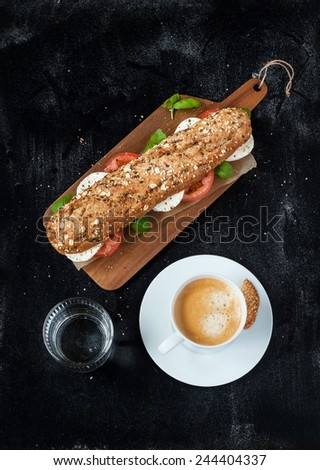 Sandwich (mozzarella cheese, tomatoes and fresh basil), coffee and water on black chalkboard background. Cafe table from above. Poster layout with free text space. - stock photo