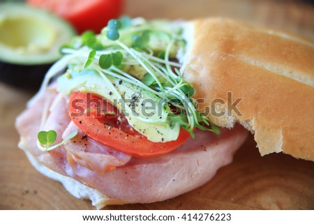 Sandwich of ham, tomato, avocado and sprouts with black pepper - stock photo