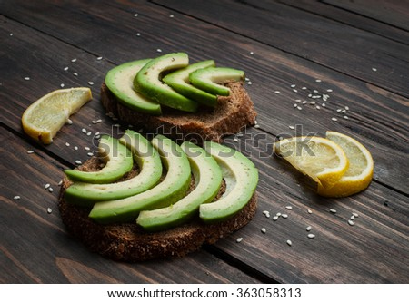 sandwich of rye bread with avocado and lemon on wood - stock photo