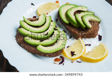 sandwich of rye bread with avocado and lemon. tinting. selective focus - stock photo