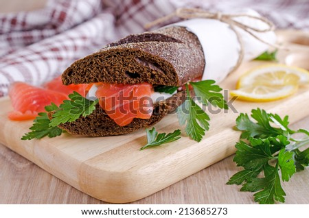 Sandwich of salted salmon and eggs on rye bread - stock photo