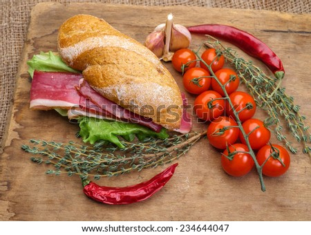 Sandwich on a wooden cutting board with slices of bacon and lettuce. Cherry tomatoes and thyme. - stock photo