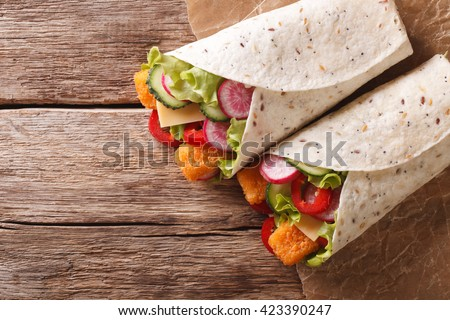 Sandwich roll with fish fingers, cheese and vegetables close-up on the table. horizontal view from above