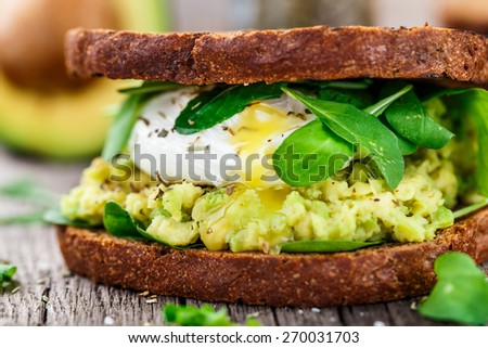 Sandwich with avocado and poached egg - stock photo