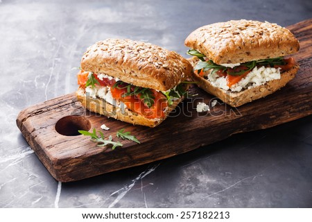 Sandwich with cereals bread and salmon on dark marble background - stock photo