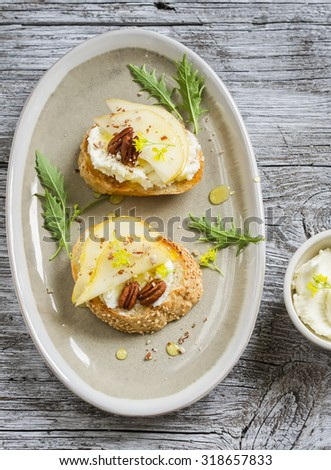 sandwich with cheese, pear, honey and nuts on the oval plate on a light wooden surface - stock photo