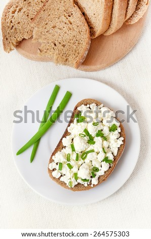 Sandwich with curd cheese and green onion on white plate, top view - stock photo