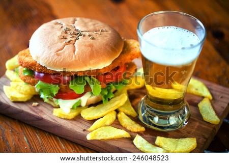 Sandwich with cutlet, fried potatoes and beer - stock photo