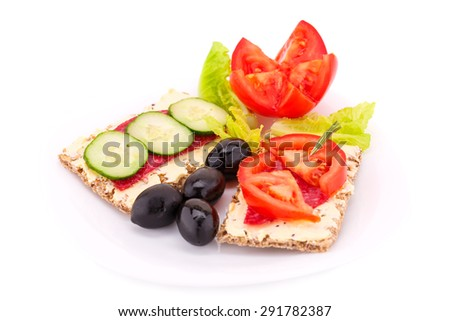Sandwich with fresh vegetables, salami and butter on plate. - stock photo