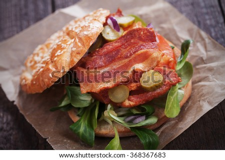 Sandwich with fried bacon, tomato and pickles - stock photo