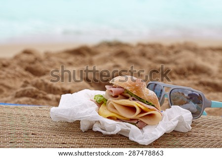 Sandwich with ham and cheese on a beach - stock photo