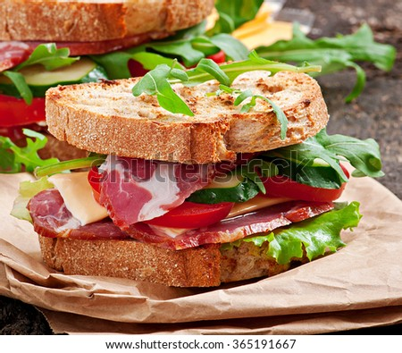 Sandwich with ham, cheese and fresh vegetables - stock photo