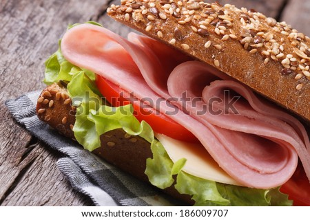 Sandwich with ham, cheese and vegetables close up on an old table. horizontal  - stock photo