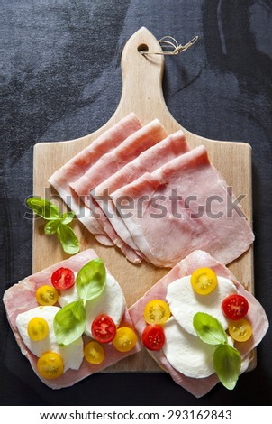 sandwich with ham, cherry tomatoes, green and black olives, basil. on old wooden board. - stock photo