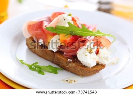 Sandwich with ham, fresh peach and soft goat cheese on white plate - stock photo