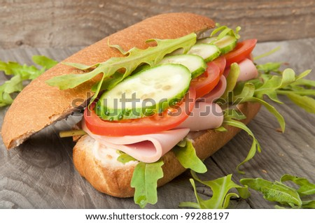 Sandwich with ham, tomato, cucumber and arugula on the old wooden cutting board - stock photo