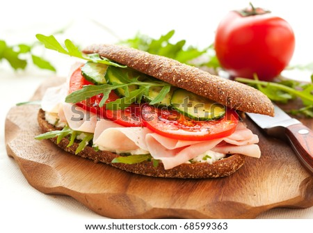 Sandwich with ham,tomato, cucumber and arugula on the wooden cutting board - stock photo