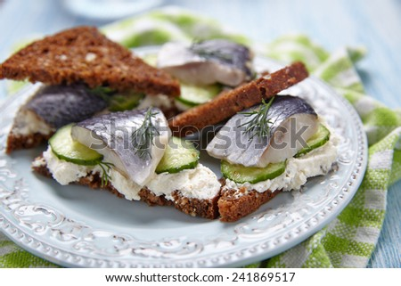 Sandwich with herring, cucumber and soft cheese - stock photo